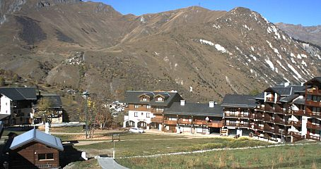 ski pistes and buildings with mountains in the background